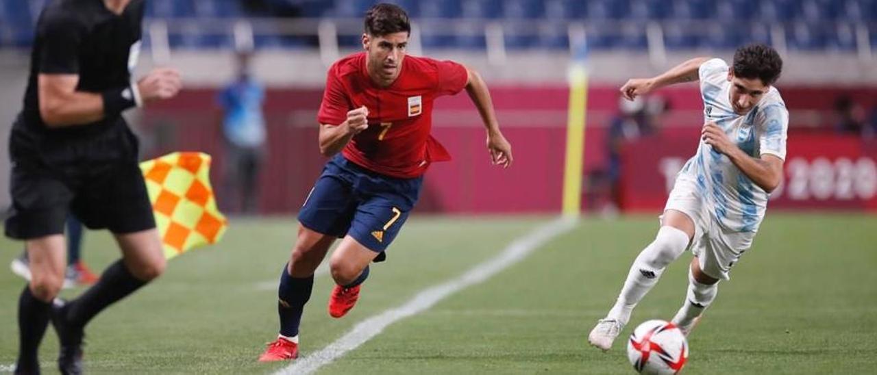 Marco Asensio, perseguido por el defensa argentino Bravo