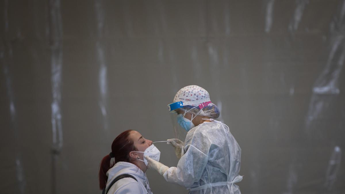 Una trabajadora sanitaria realiza un test de antígenos a una joven.