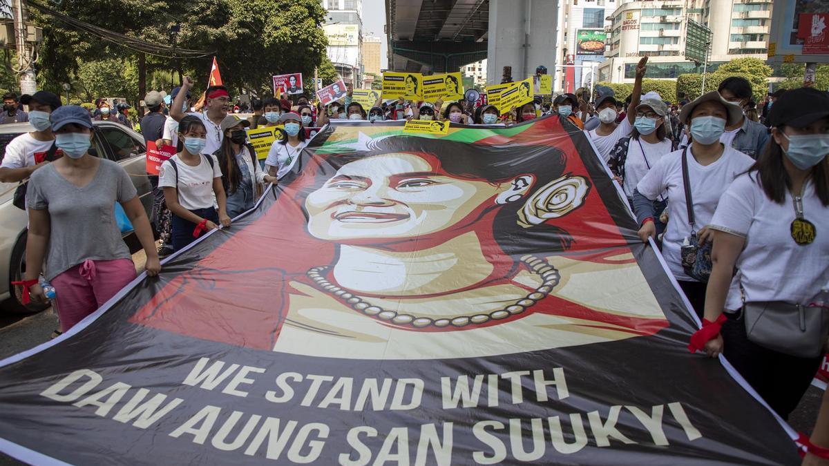 Manifestantes sujetan un cartel con una ilustración que representa a Aung San Suu Kyi.