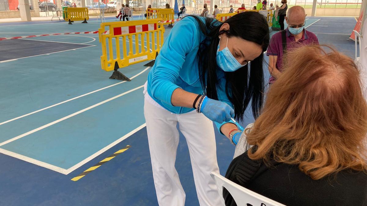 Una enfermera vacuna a una mujer en el pabellón polideportivo de Bellreguard esta semana