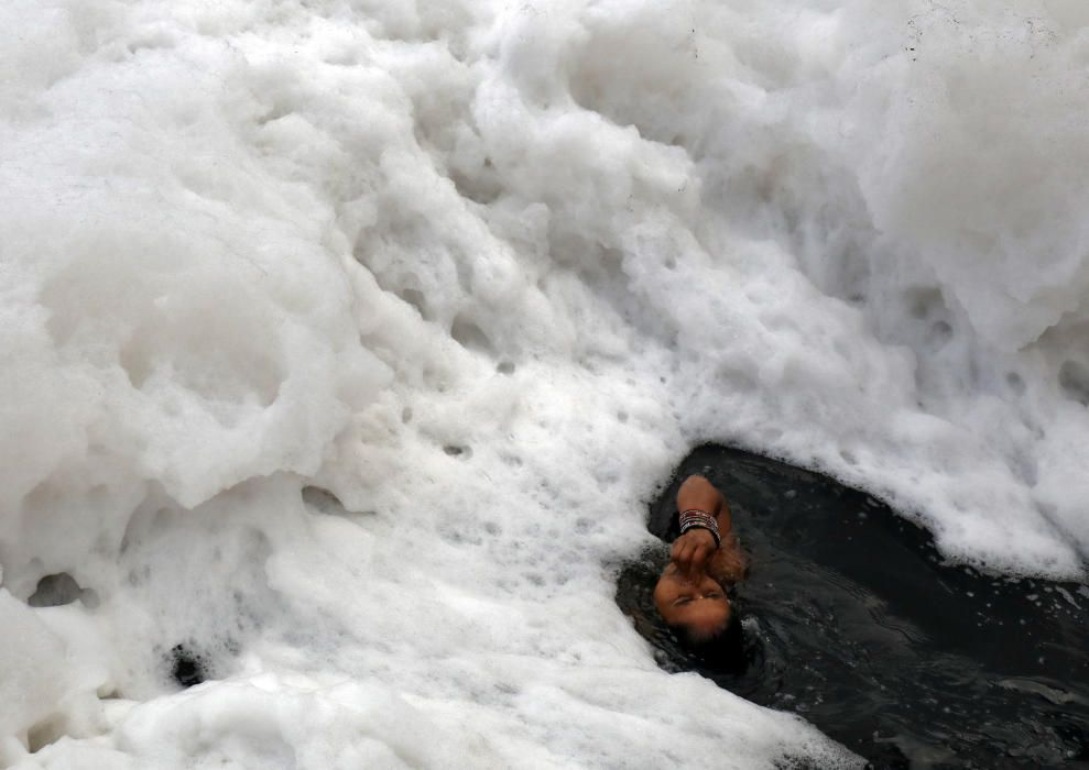 A Hindu woman takes a dip in the polluted waters ...