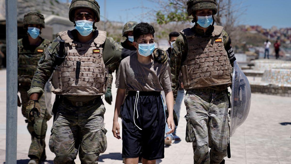 Dos militares acompañan a un menor a la frontera con Marruecos, en Ceuta.