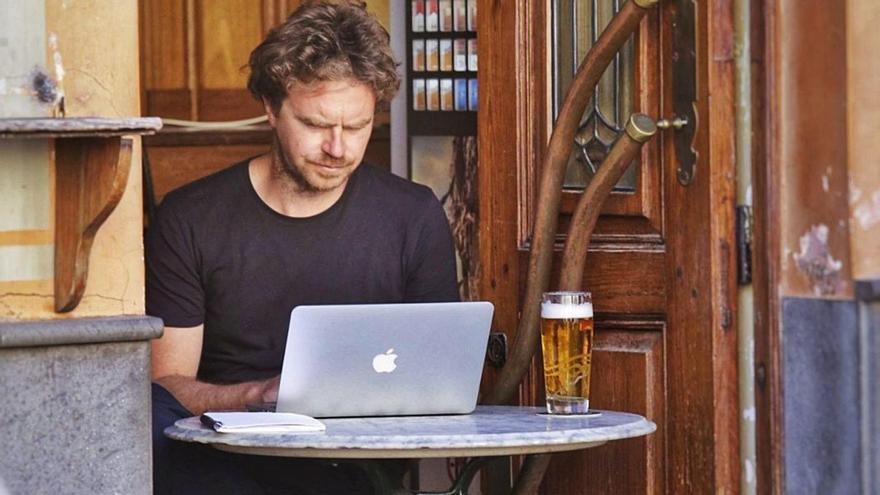 Un teletrabajador se conecta al portátil en una cafetería de La Laguna.