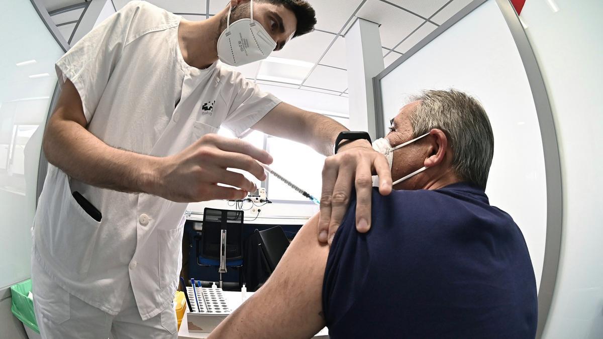 Un sanitario vacuna a un hombre en Alcalá de Henares.