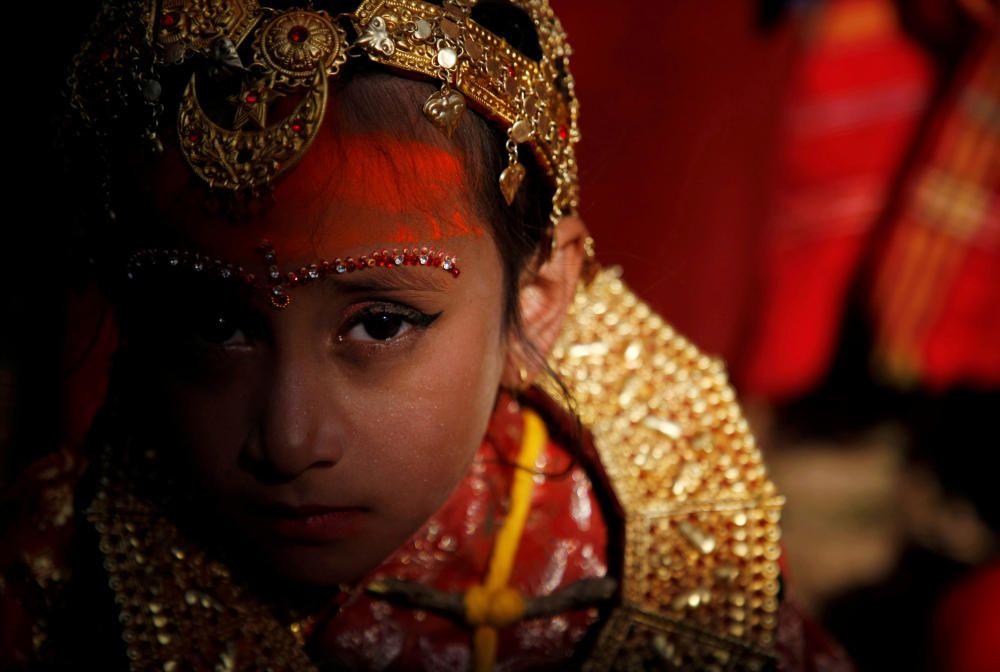 Light illuminates a Newari girl as she takes ...