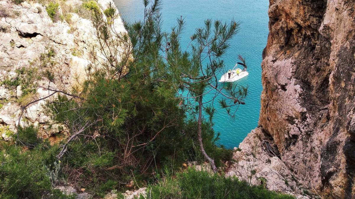 Punto por el que ha caído el vehículo hasta el mar; abajo, la embarcación de la Policía Local