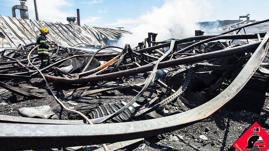 Empresa y bomberos inician el desmontaje de la nave calcinada en San Vicente hace un mes