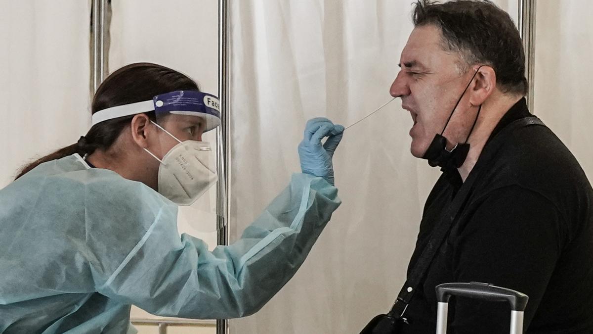 Una enfermera haciendo una PCR a un paciente.