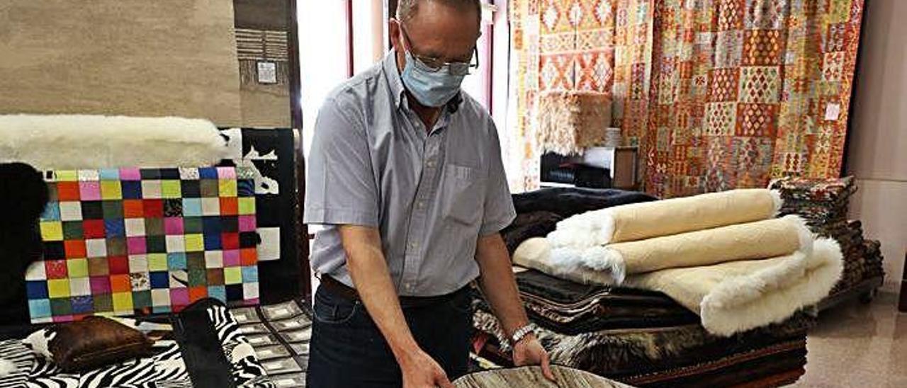 Francisco Ferrández enseña algunos modelos de alfombras en su tienda de Crevillent.