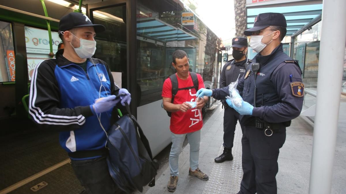 La Policía Local de Alicante repartiendo mascarillas esta mañana en una parada de autobús en Alicante.