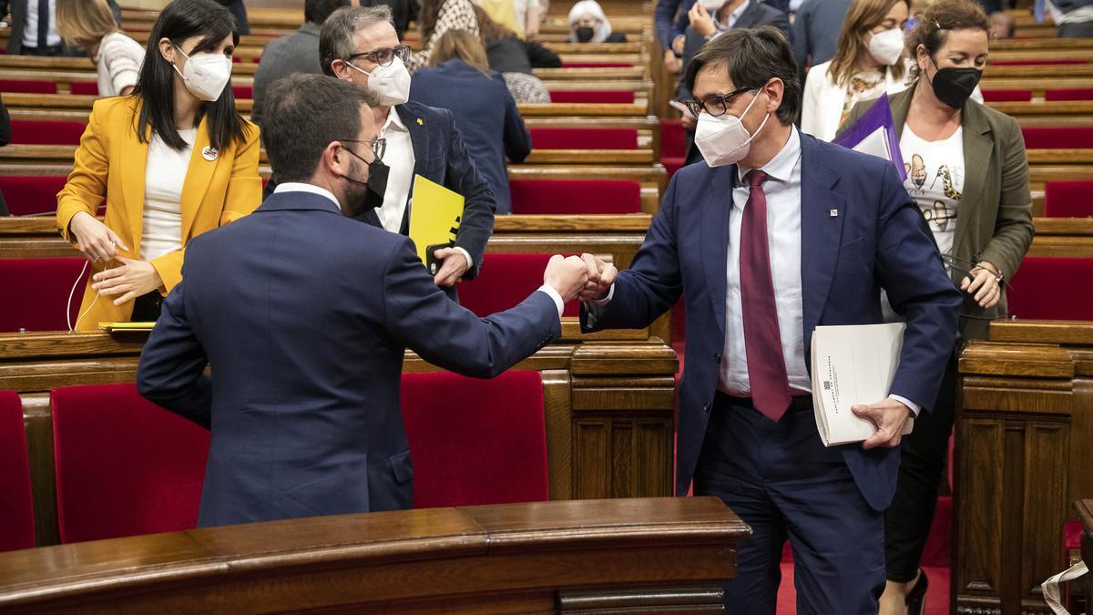 Pere Aragonès xoca el puny amb el portaveu del PSC, Salvador Illa, durant el ple del Parlament del 20 de maig