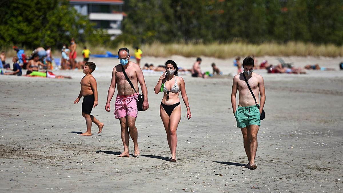 Personas con mascarilla en una playa galega, el pasado verano. |   // GUSTAVO SANTOS