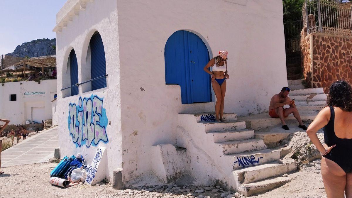 Una bañista posa en la puerta azul. Las pintadas están en la pared que mira al mar, en los escalones y en un pequeño contrafuerte