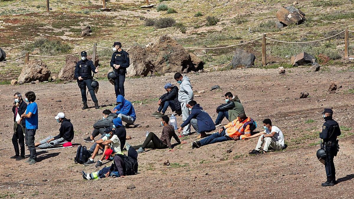 Un grupo de migrantes es custodiado por agentes de la Policía Nacional tras ser desalojados ayer del Confital. | | EFE