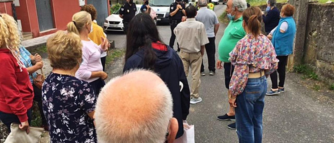 Vecinos frente al cordón policial que ayer protegió los trabajos de instalación de la torre de alarma en el barrio de Arcade.   | // AVV O CONDE