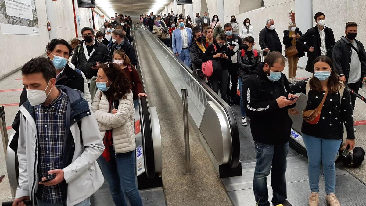 Largas colas de residentes ante los controles covid-19 del aeropuerto el domingo por la noche después de aterrizar en la isla.