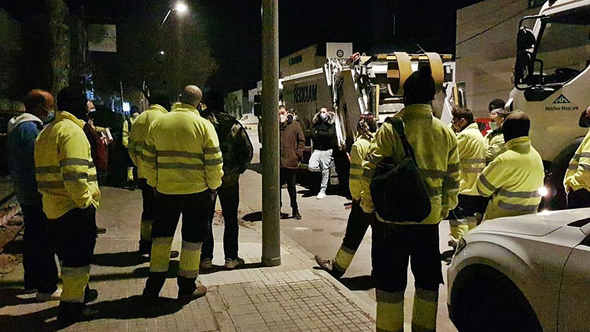 Trabajadores se reúnen ante algunos camiones que anoche no salieron en el Raiguer.