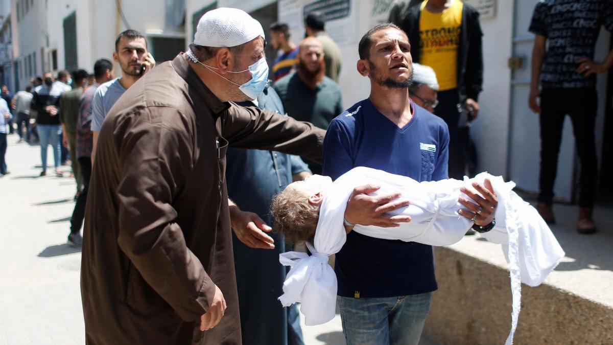 Un hombre porta el cuerpo sin vida de un niño fallecido en los bombardeos de Israel en Gaza.