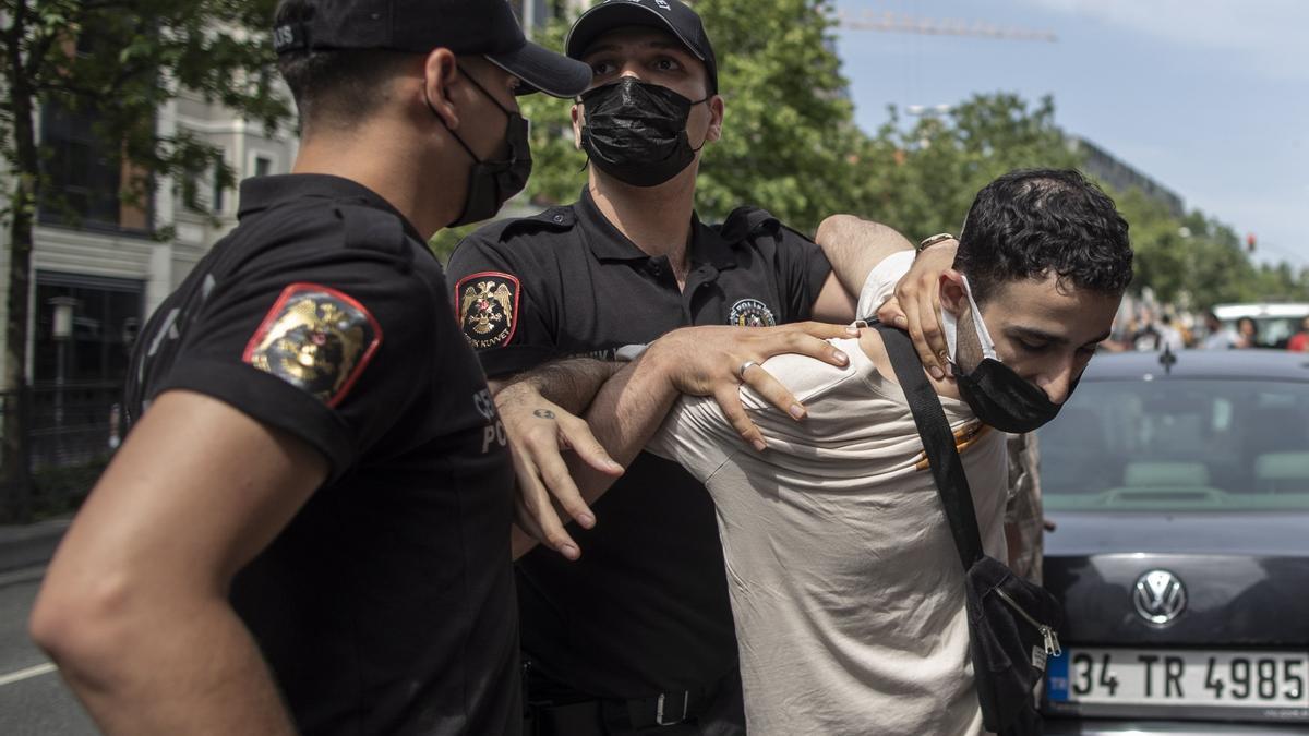 Dos agentes turcos se llevan detenido a un manifestante.