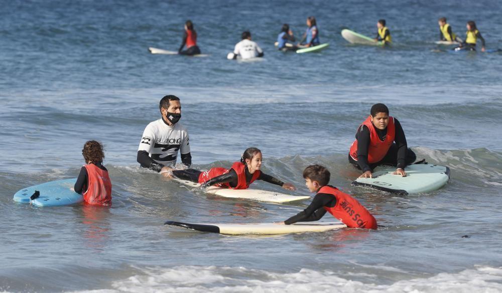 Niños y niñas practicando surf en la playa de Patos. // R. Grobas
