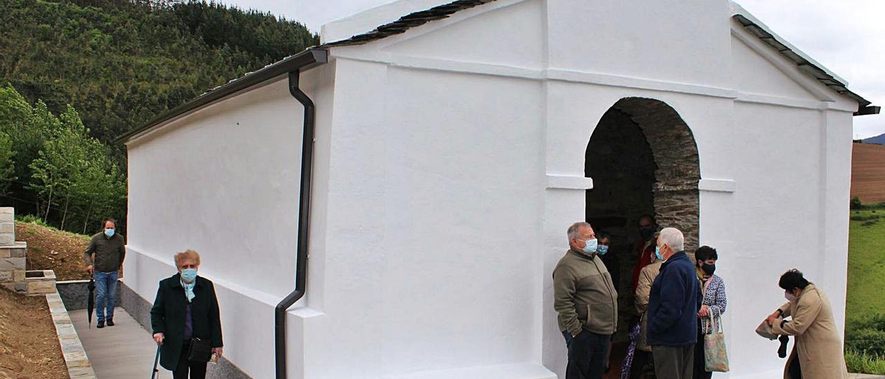 Vecinos llegando la capilla, arreglada y con una nueva fuente en el lateral. En el círculo, Isabel Méndez con una rosca. | T. C.