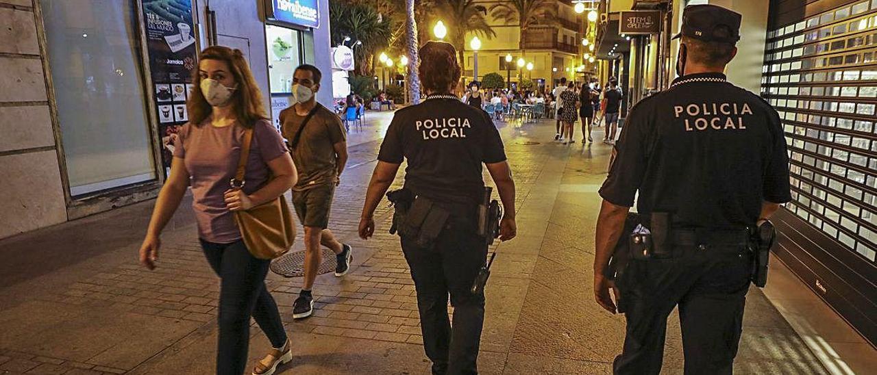 Ciudadanos con mascarilla por Elche y agentes de la Policía Local, en una imagen reciente.
