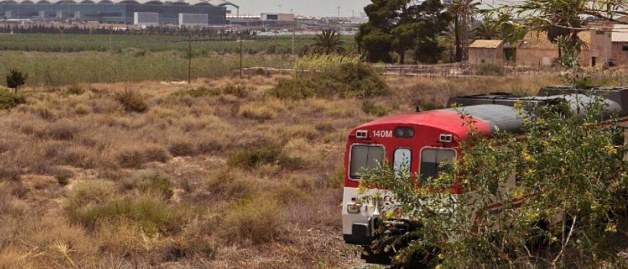 Un tren de cercanías y el aeropuerto al fondo.
