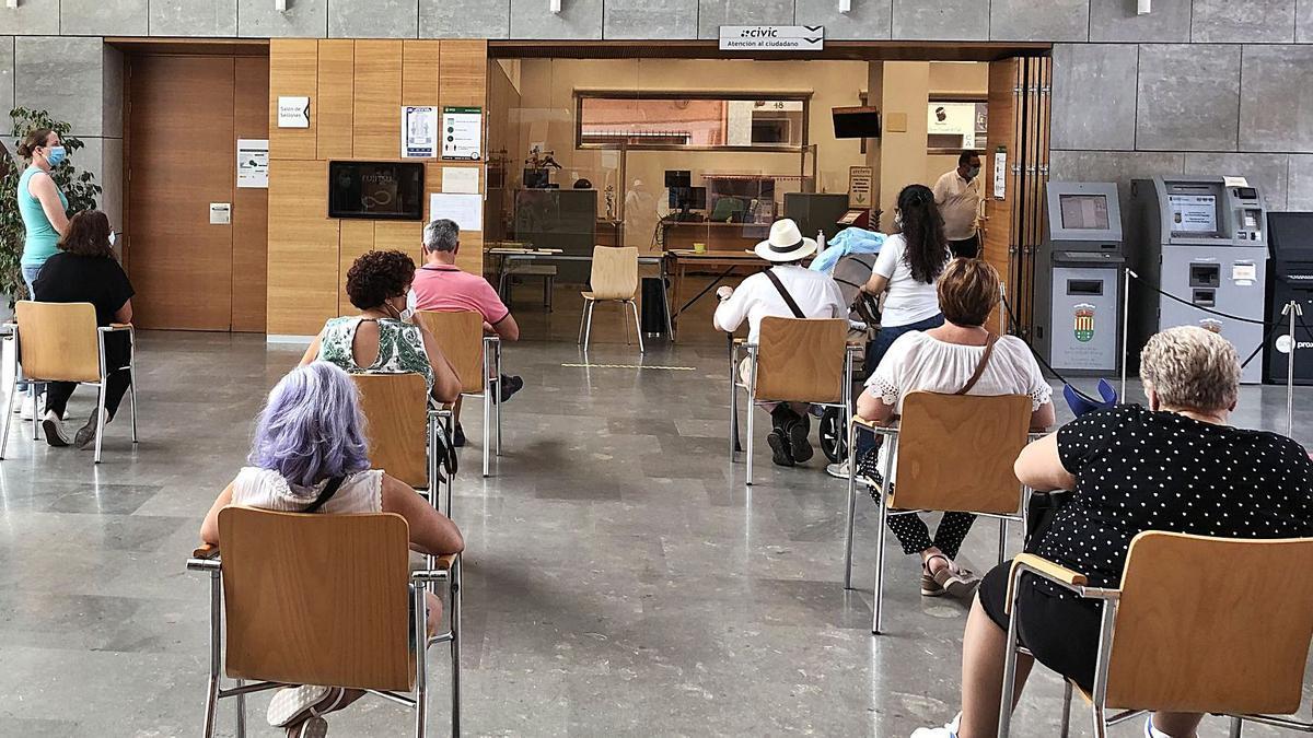 Varias personas esperan ante el Civic para ser atendidos con cita previa en el hall del Ayuntamiento de San Vicente.