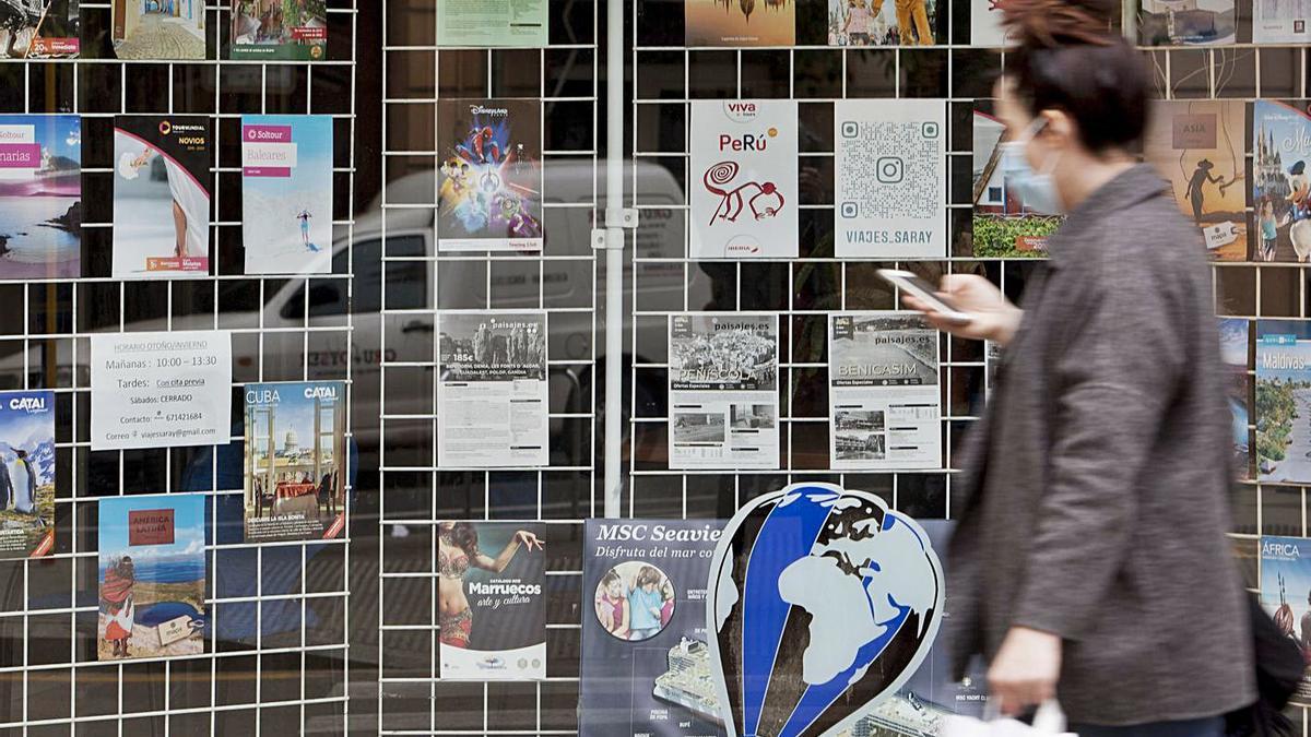 Una mujer pasa por delante de una agencia de viajes, ayer en València. | FERNANDO BUSTAMANTE