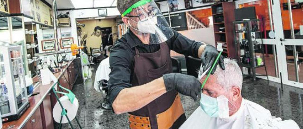 El peluquero Pablo Monzón corta el pelo a un cliente en la primera jornada de la desescalada, en su barbería de Puerto del Rosario.