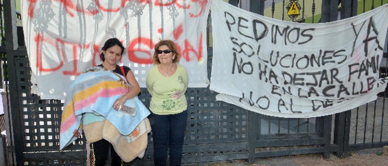 Cathaisa Santana con su bebé nacido el pasado 26 de diciembre junto a Mari Carmen Martel al lado de las pancartas en la urbanización de Sardina.