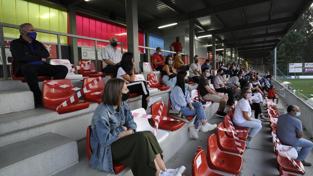 Imagen de un partido de pretemporada con separación de seguridad entre aficionados.