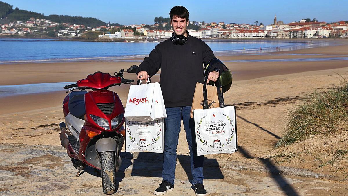 """Fidel Fernández, el """"rider"""" oficial, con bolsas de comida junto a su moto en Praia América.     // RICARDO GROBAS"""