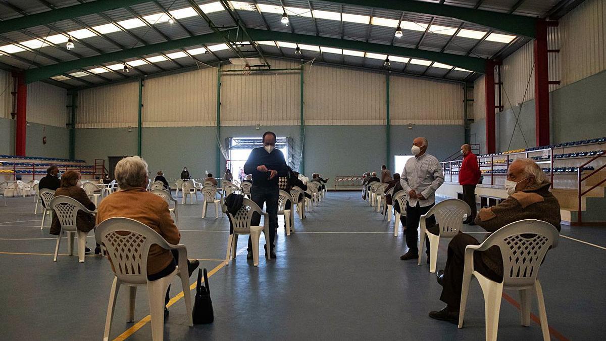 Vecinos citados esperando su turno en el pabellón deportivo para recibir la vacuna.   José Luis Fernández