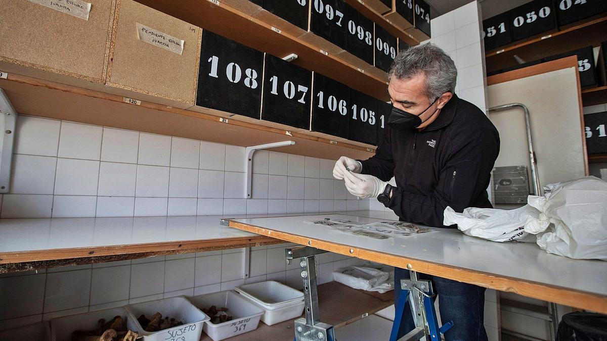 El antropólogo social de la asociación AMEDE, Javier Pérez trabaja en el almacén donde se depositan los restos y las pertenencias de los exhumados   ROMÁN RÍOS ( EFE)