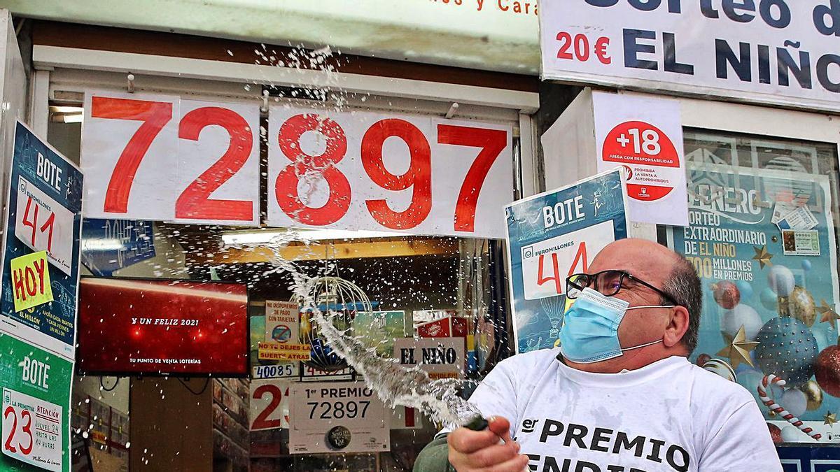 Juan descorcha el champán tras recibir la noticia de la venta de un décimo del Gordo. |   // MARTA G. BREA