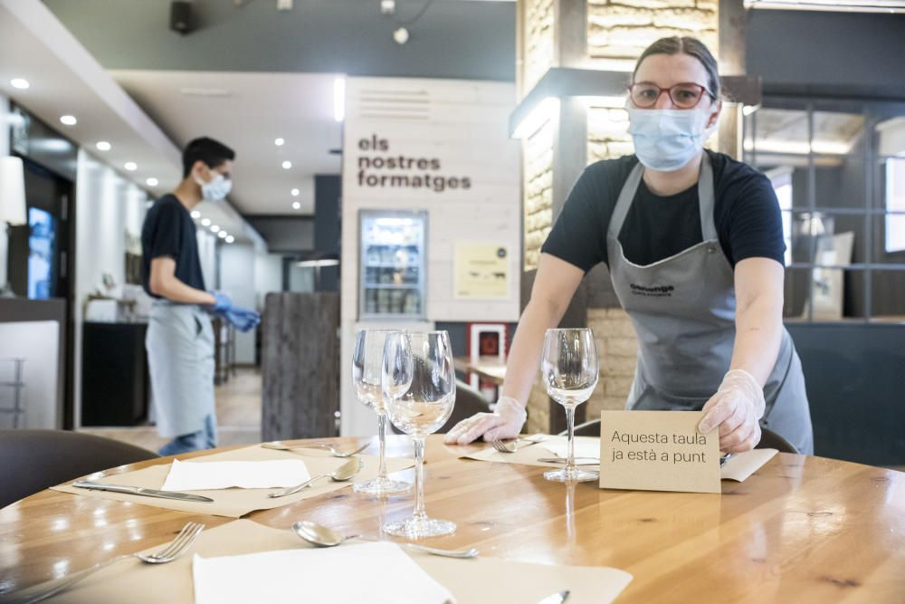 Els treballadors del restaurant El Canonge preparen el menjador abans que arribin els clients.