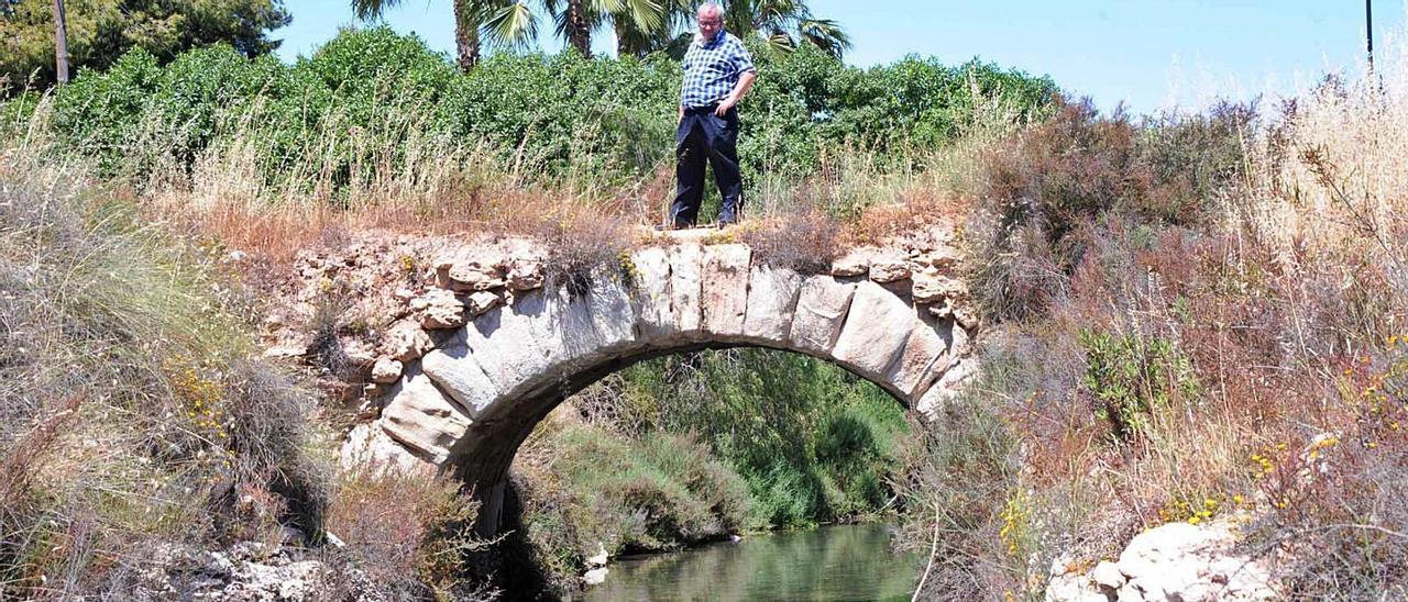 El canal del Acequión, que está repleto de enseres y residuos, y el puente de sillería, en las cercanías del parque de la Estación