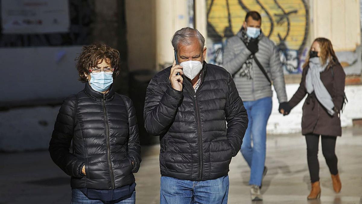 Viandantes en el centro de València con ropas de abrigo.   LEVANTE-EMV