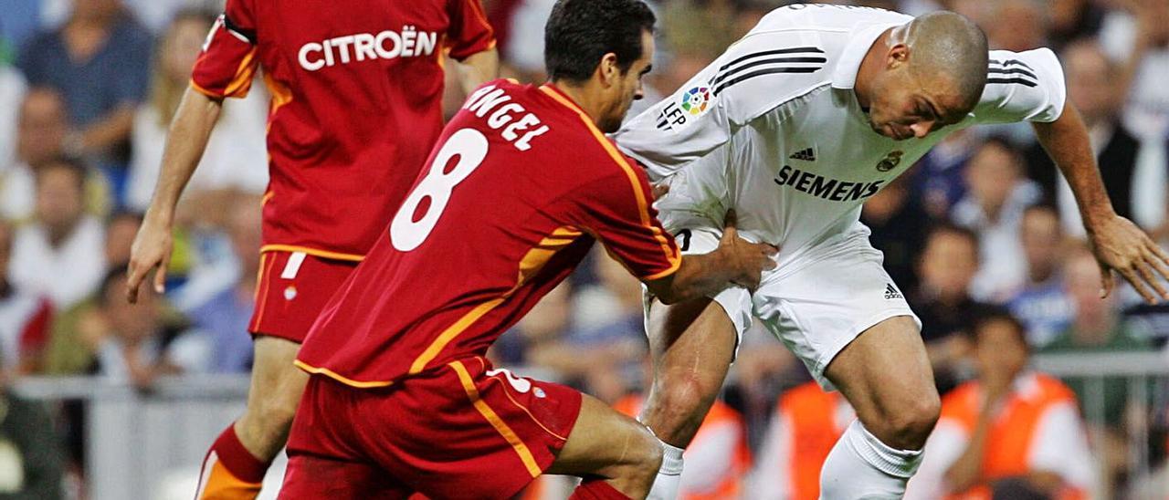 Ángel López sujeta a Ronaldo en presencia de Antonio Núñez en el partido disputado en 2006.    // REUTERS