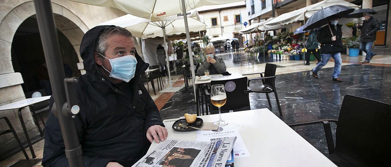 Juan Hevia leyendo LA NUEVA ESPAÑA, en una terraza hostelera de la calle Quintana, ayer, en pleno chaparrón. | Miki López