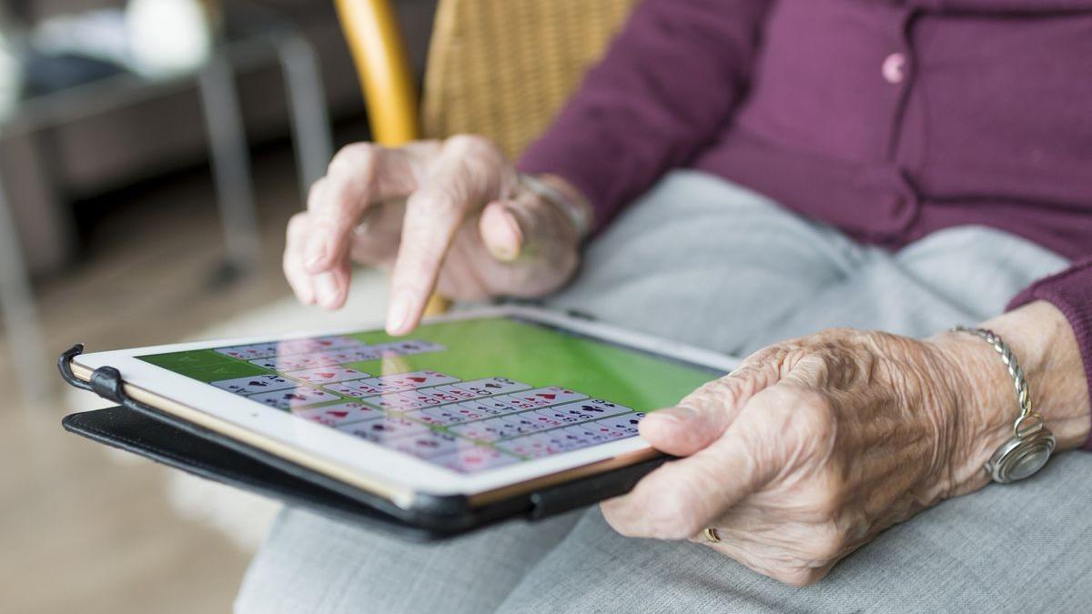 Una mujer mayor maneja una tableta inteligente.