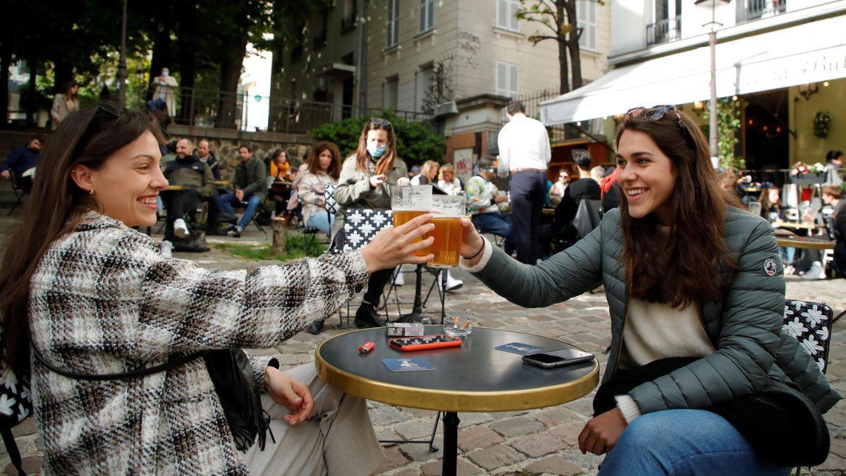 Dos jóvenes consumen en una terraza en París.