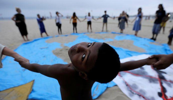 2.Un niño y activistas del cambio climático asisten a las protestas de la Rebelión de la Extinción en la playa de Copacabana