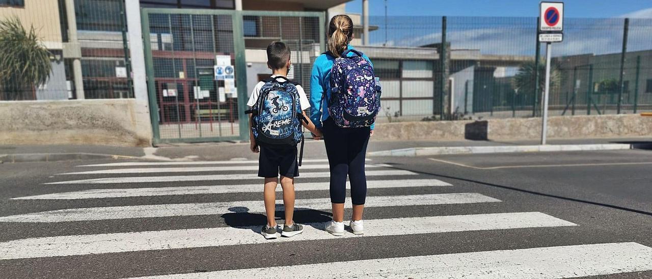 Dos escolares cruzan un paso de peatón frente a un colegio de primaria de Ingenio.