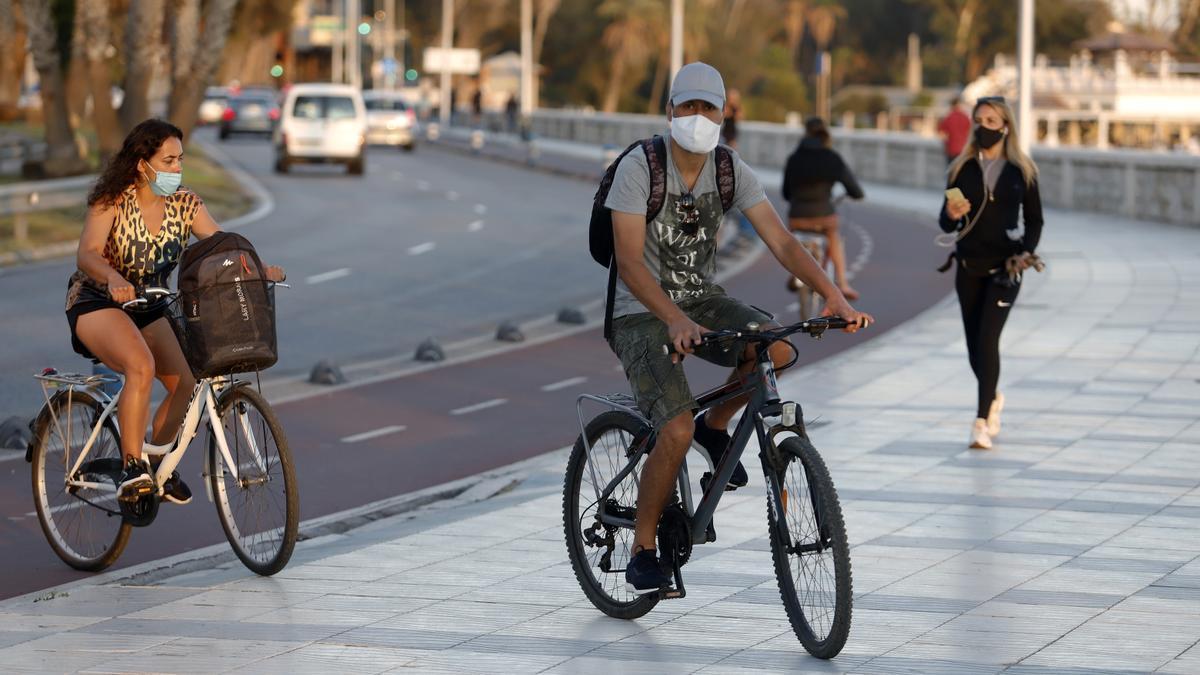 Un grupo de personas practican deportes al aire libre con mascarillas.