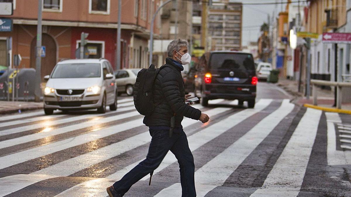 Un ciudadano provisto de su mascarilla cruza el singular paso de cebra de Algemesí. | PERALES IBORRA