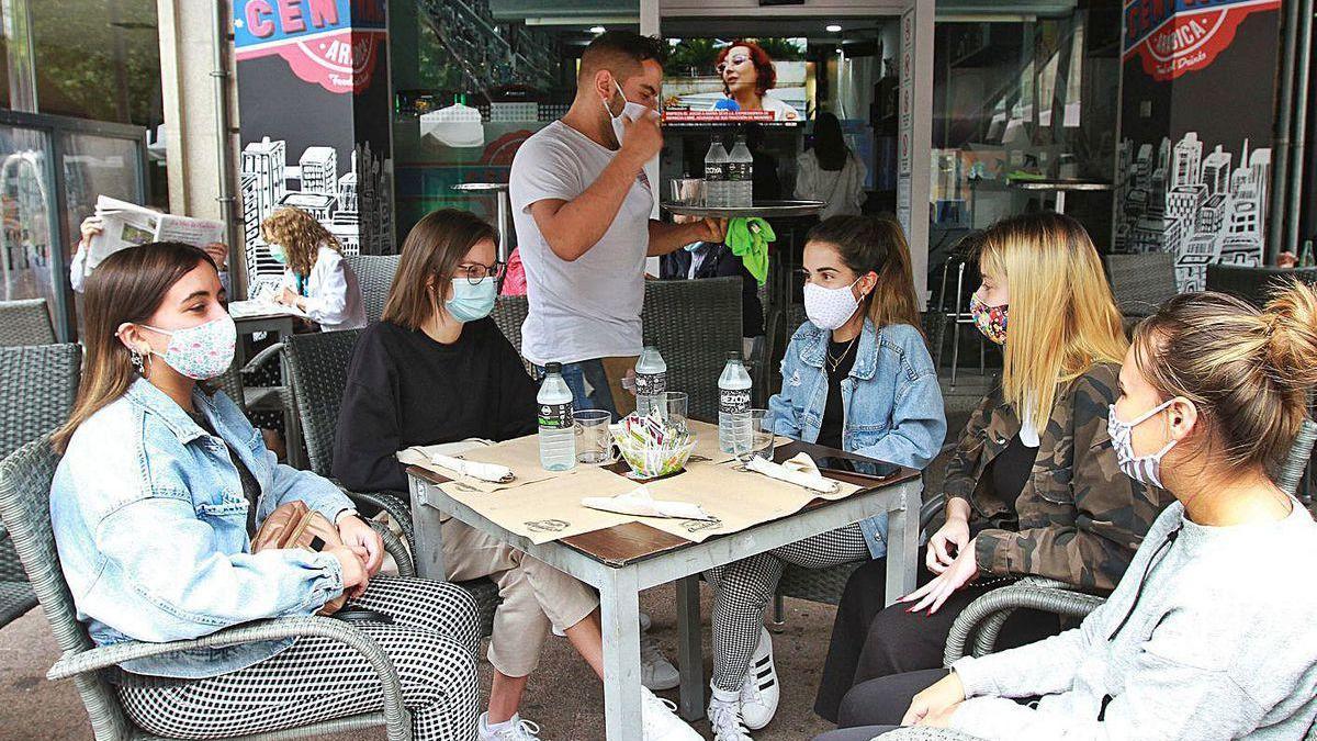 Cinco jóvenes en una terraza de un bar en el Parque de San Lázaro.