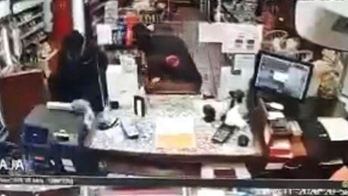 Captura de las cámaras de seguridad de la gasolinera de La Fresneda, con dos encapuchados en medio y el empleado en la esquina inferior derecha. | R. A. I.