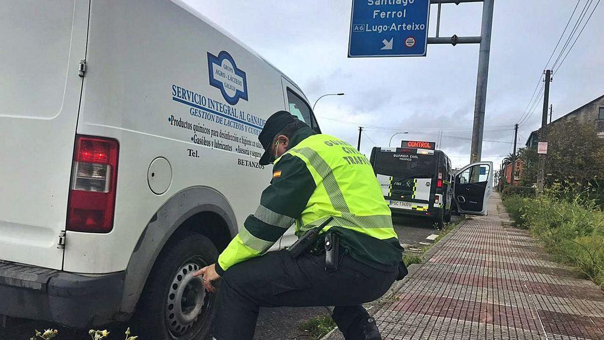 Un agente durante la campaña de control a furgonetas revisa el estado de los neumáticos.